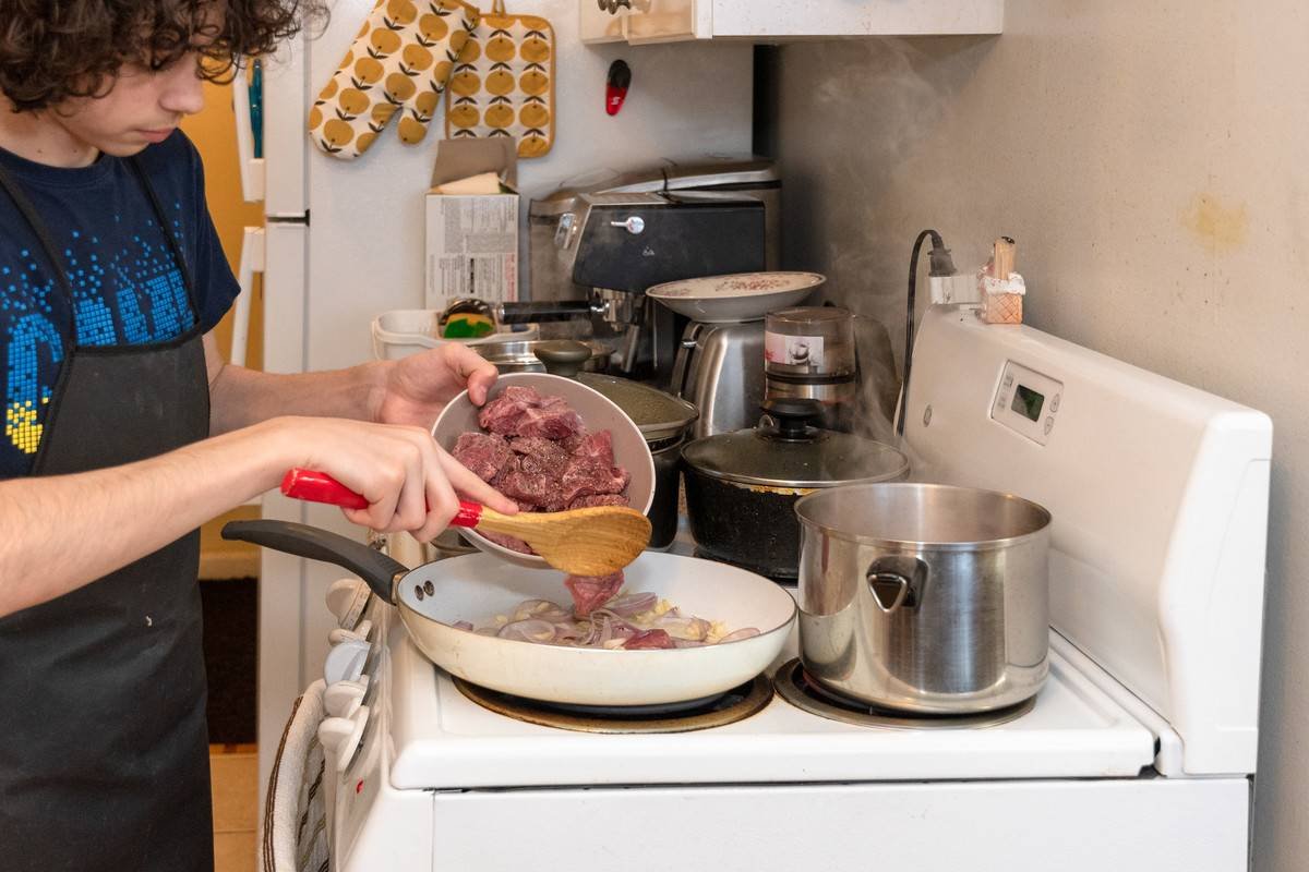 teenager cooking on stovetop