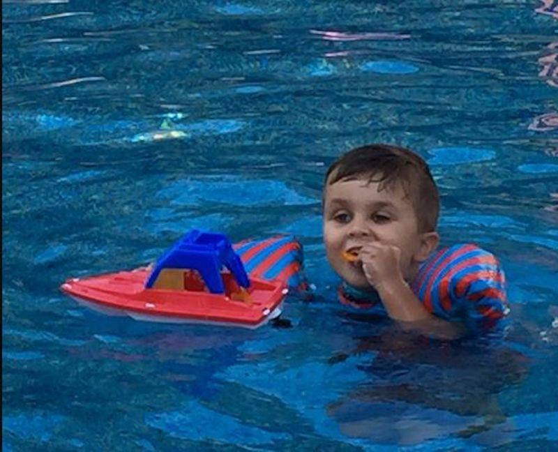 kid in swimming pool eating snacks out of boat toy