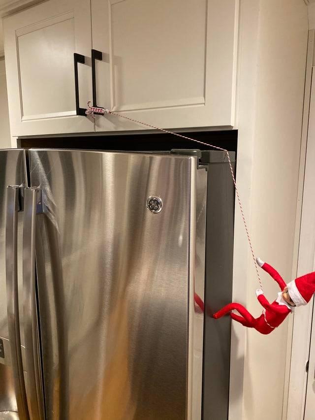 elf scaling a fridge