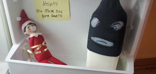 Tied up Elf on the shelf with note saying
