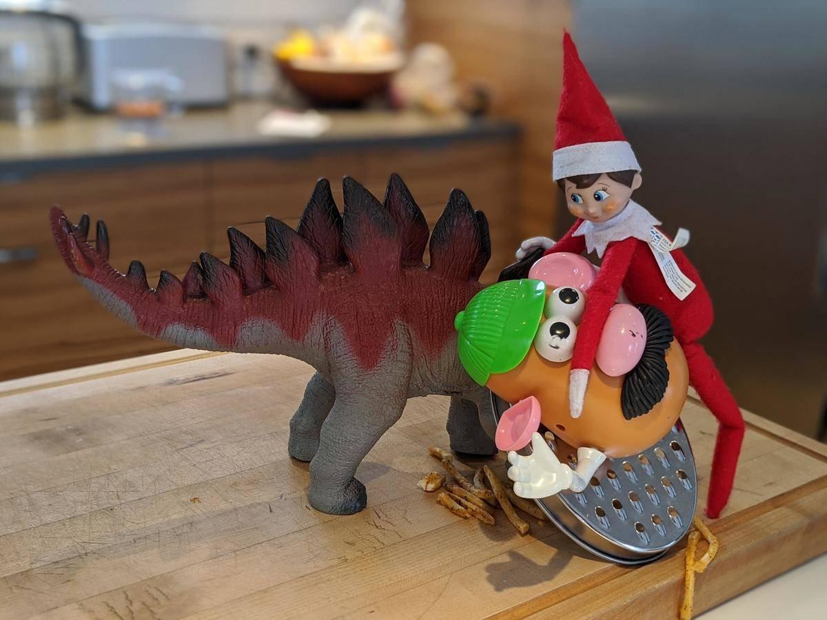 elf shredding mr. potato head on a grater