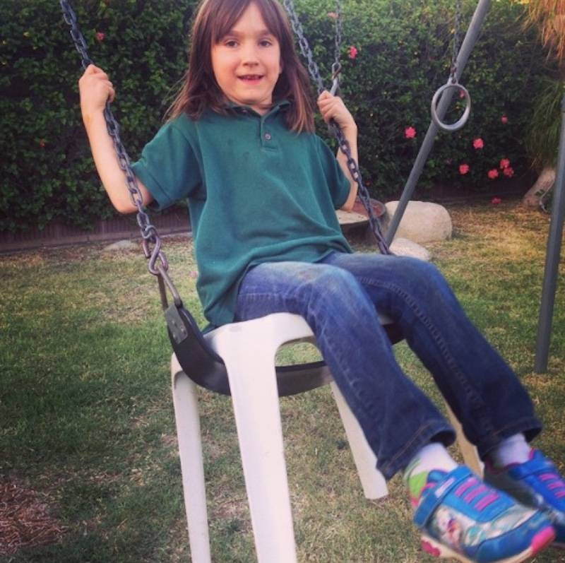 kid on swing with plastic stool over the seat