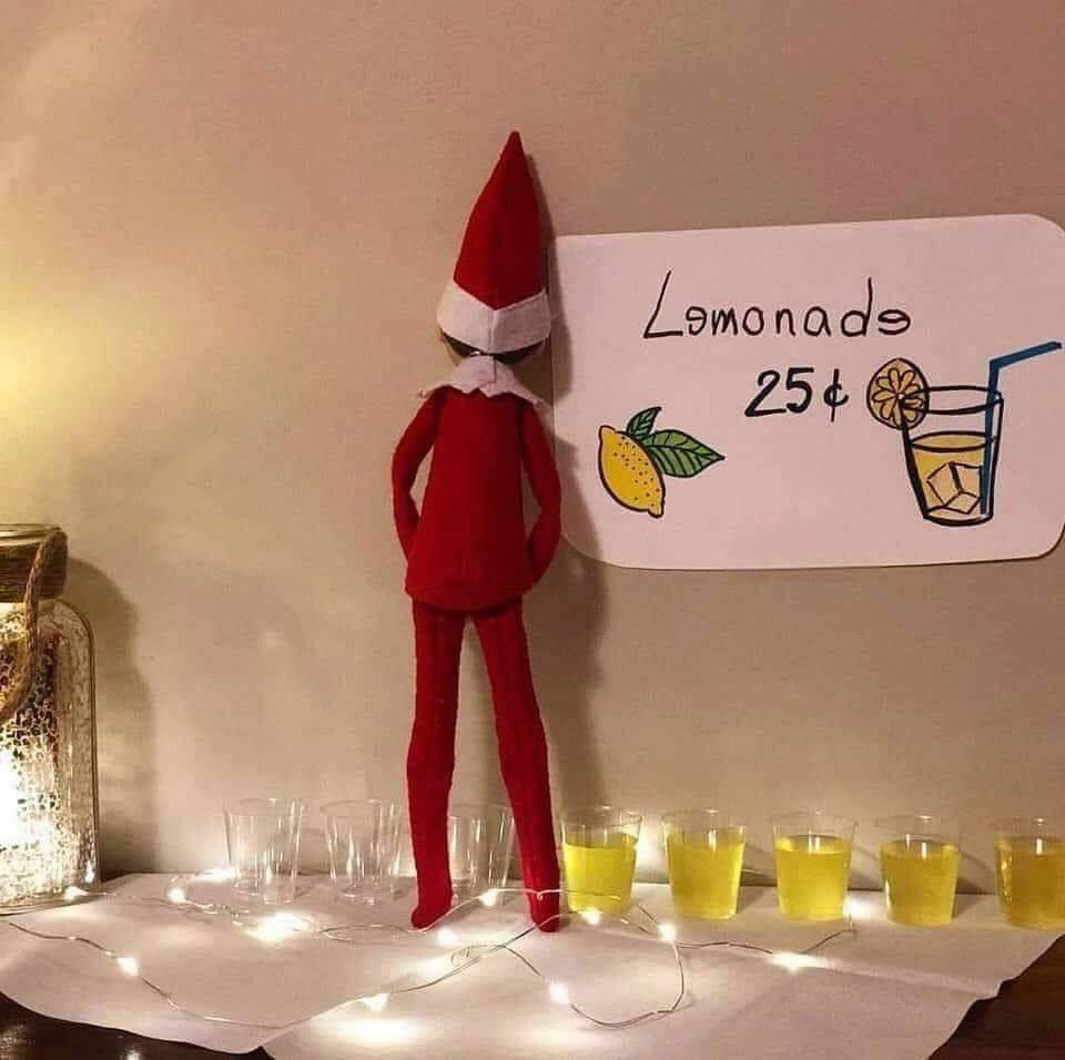 elf looks like he's peeing in cups with lemonade sign in front of him