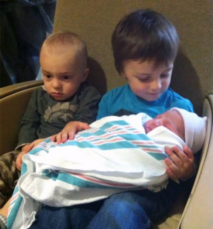 middle child looks upset as oldest sibling holds youngest