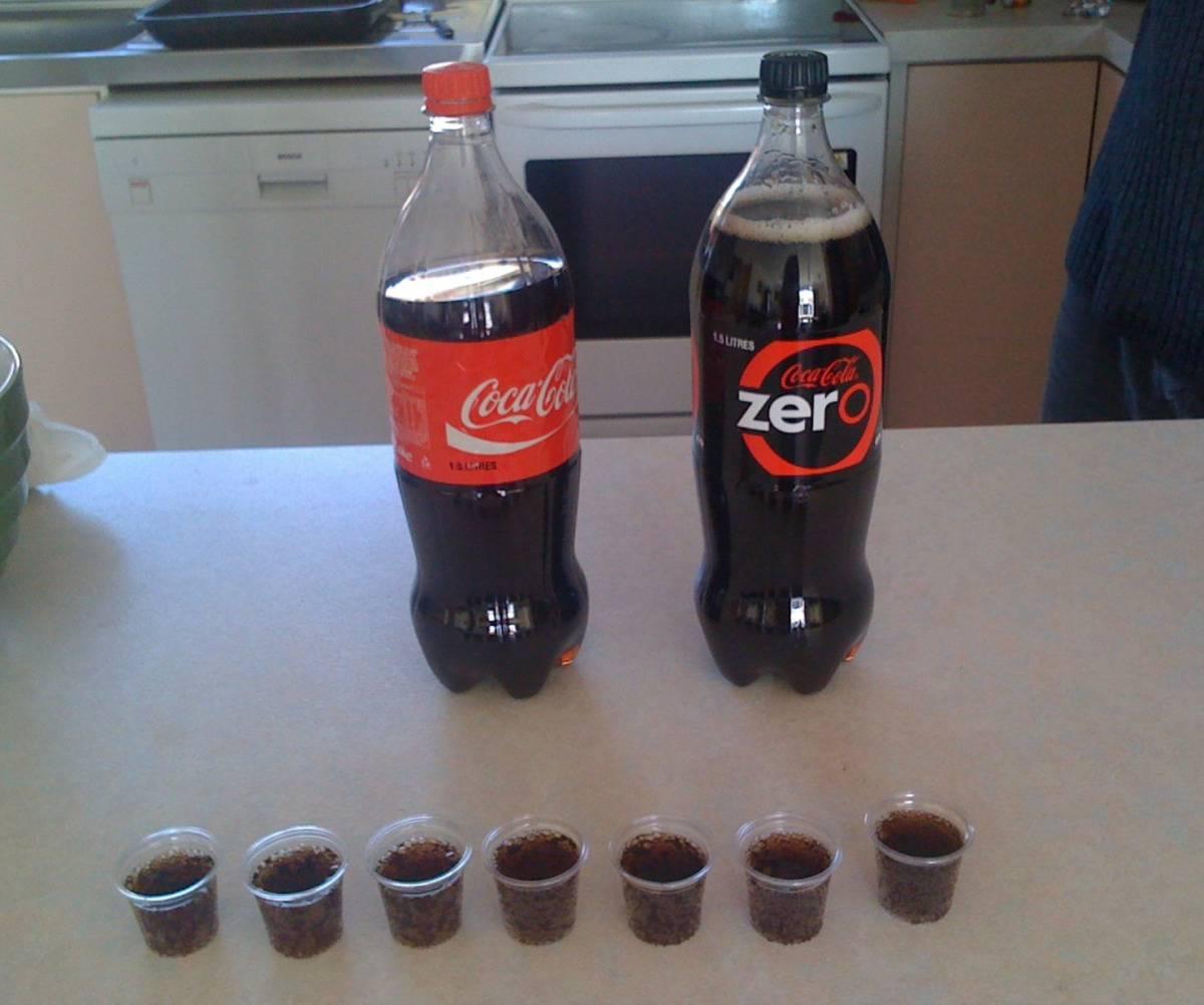 line of shot glasses full of coca cola