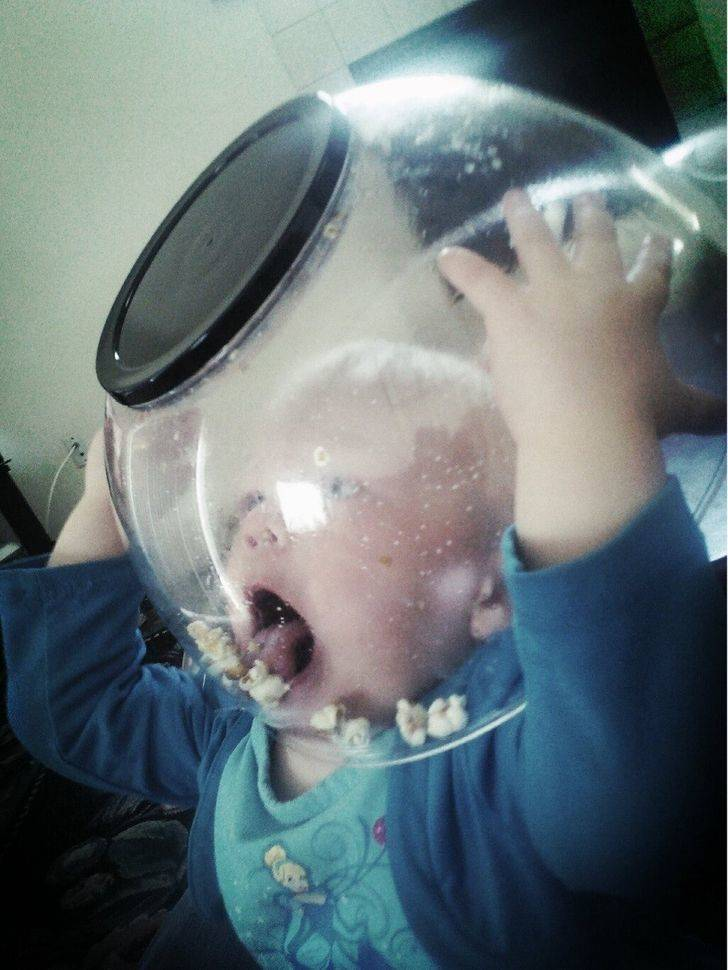 kid with popcorn bowl over head
