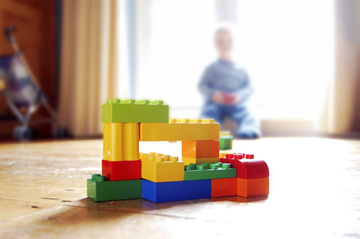 lego structure on floor with child in the background