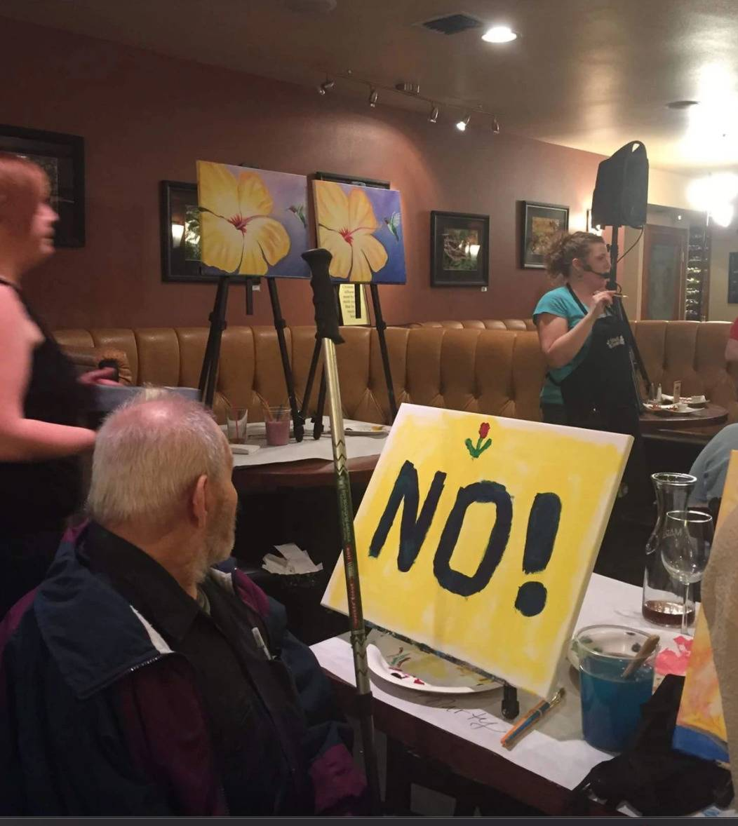 paint night with instructor painting flower and old man with canvas that just has