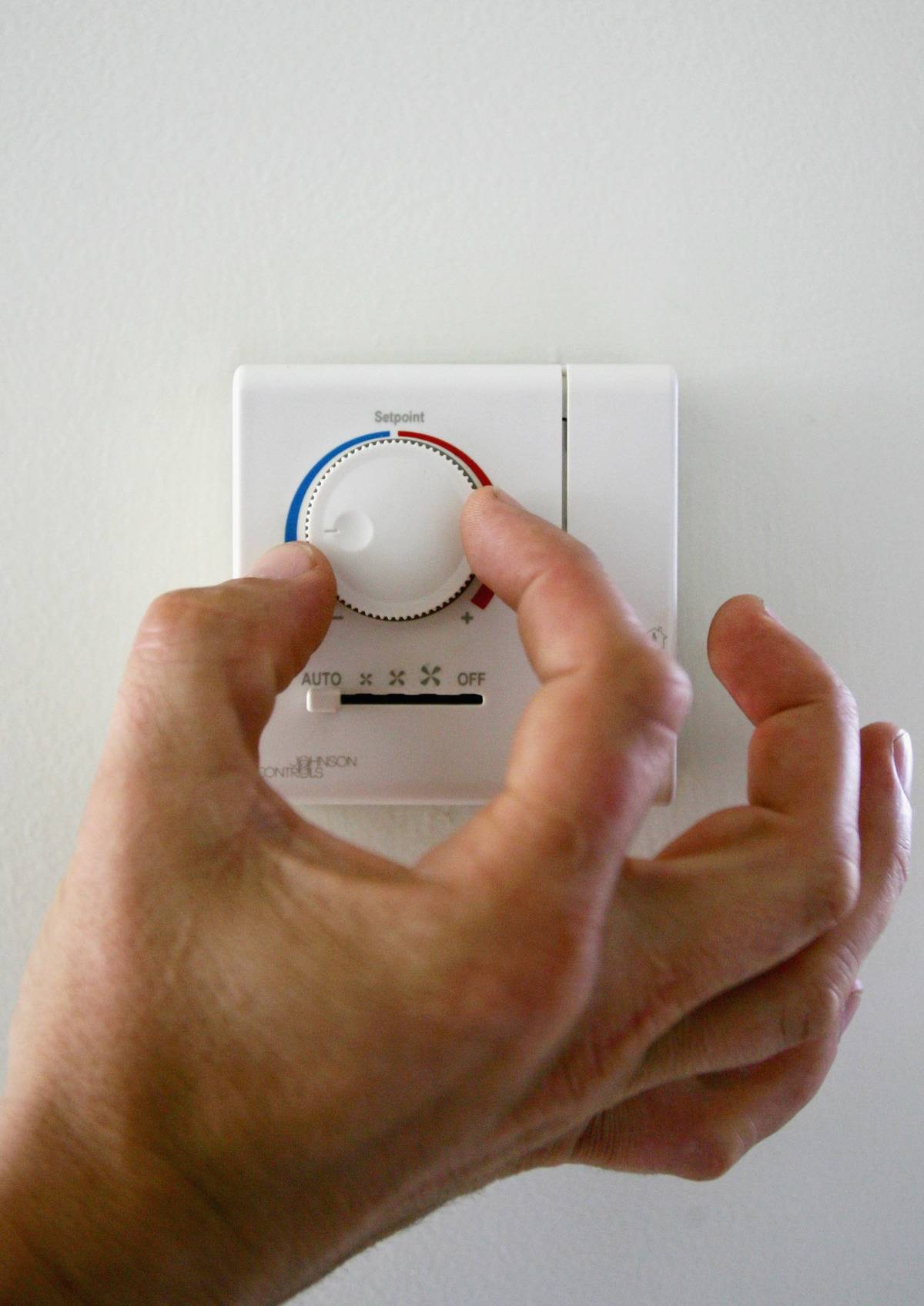 person with hand on dial of thermostat turning it cold