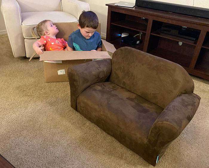 Kids sitting in the box their kid-sized couch came in