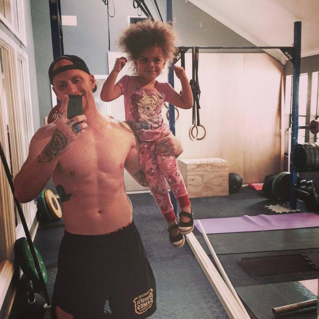 dad hoisting daughter on shoulder taking gym selfie