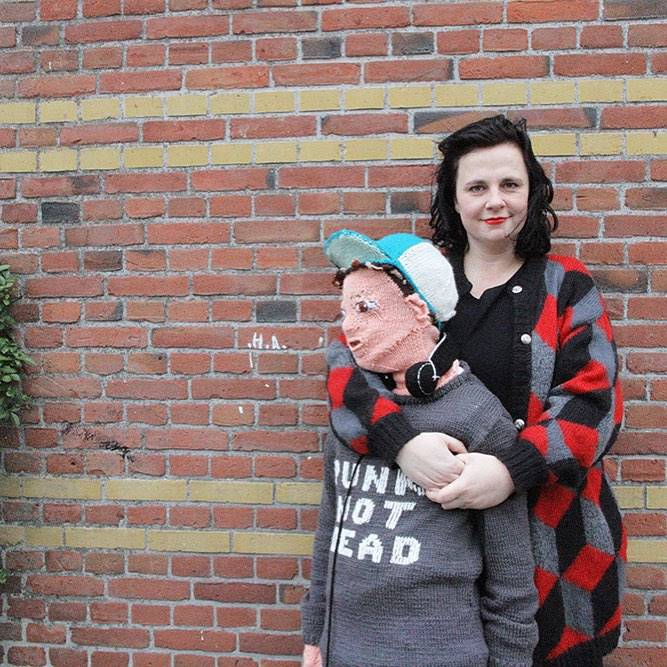 woman hugging a life size knitted son