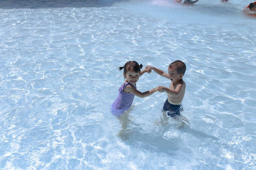 little boy and girl holding hands and smiling in a pool