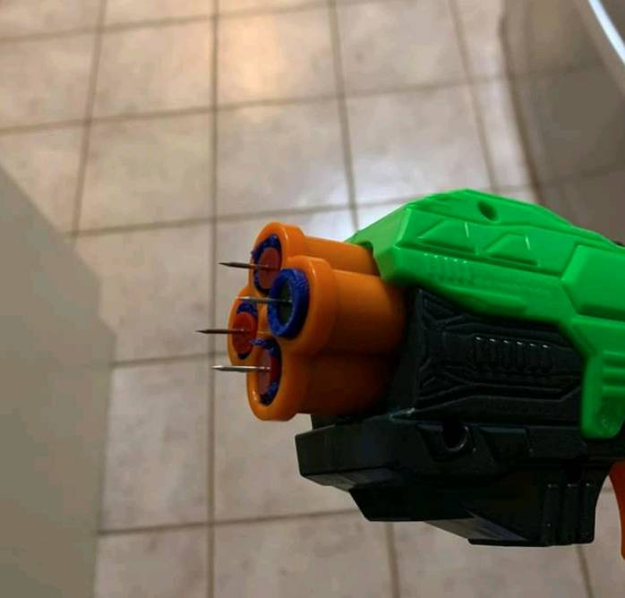 nerf gun with darts that have thumbtacks embedded at the tip with the sharp part sticking out