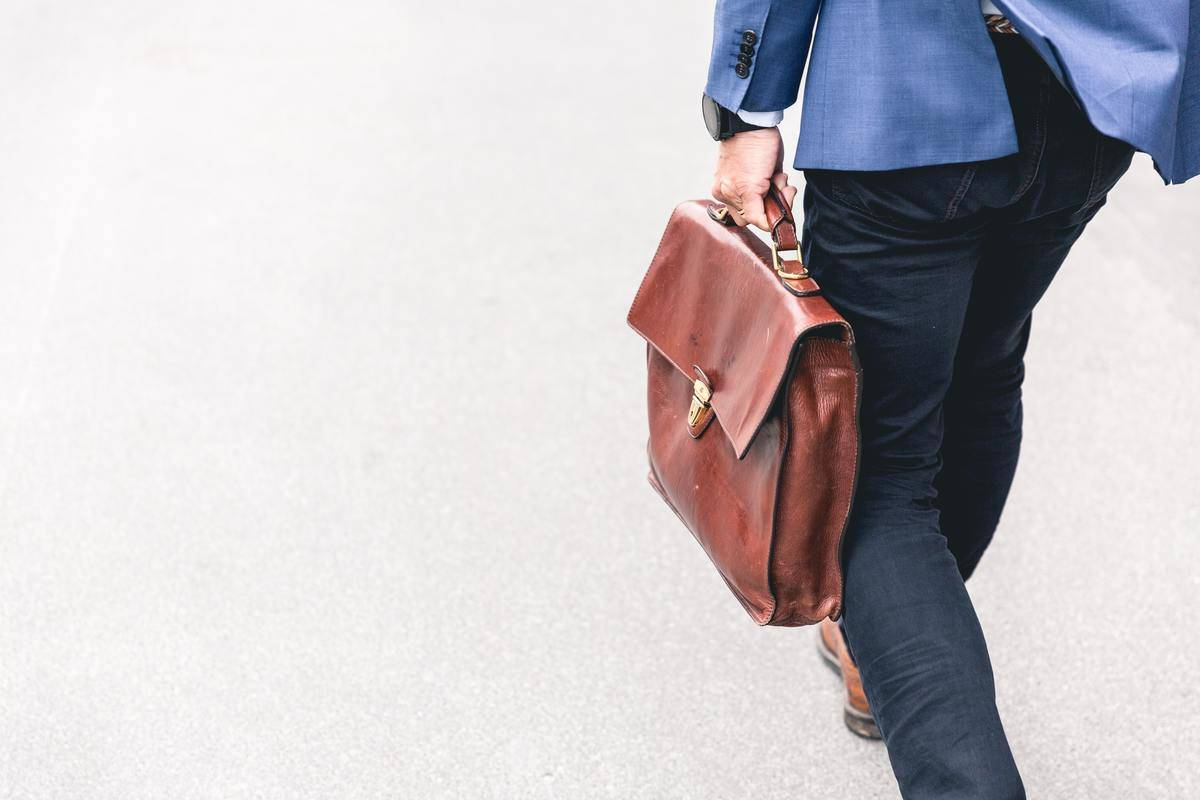 man walking with briefcase in hand