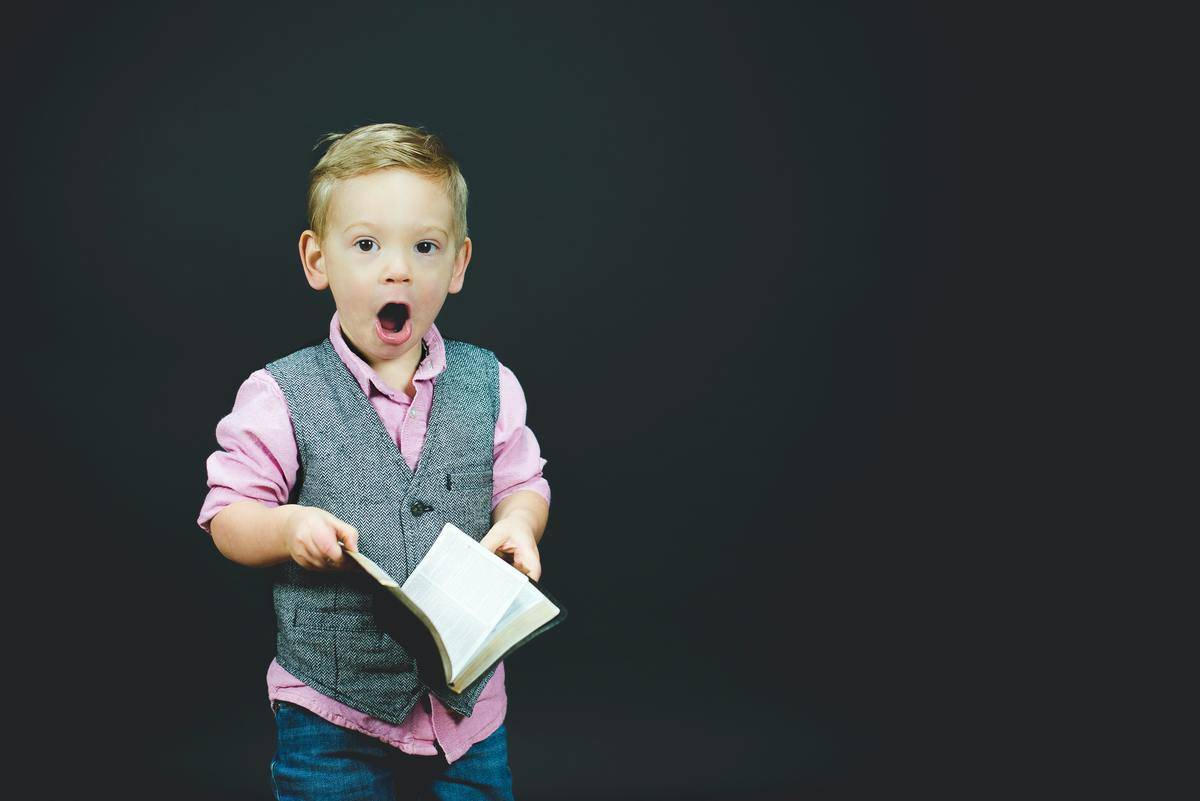 child holding book looking surprised
