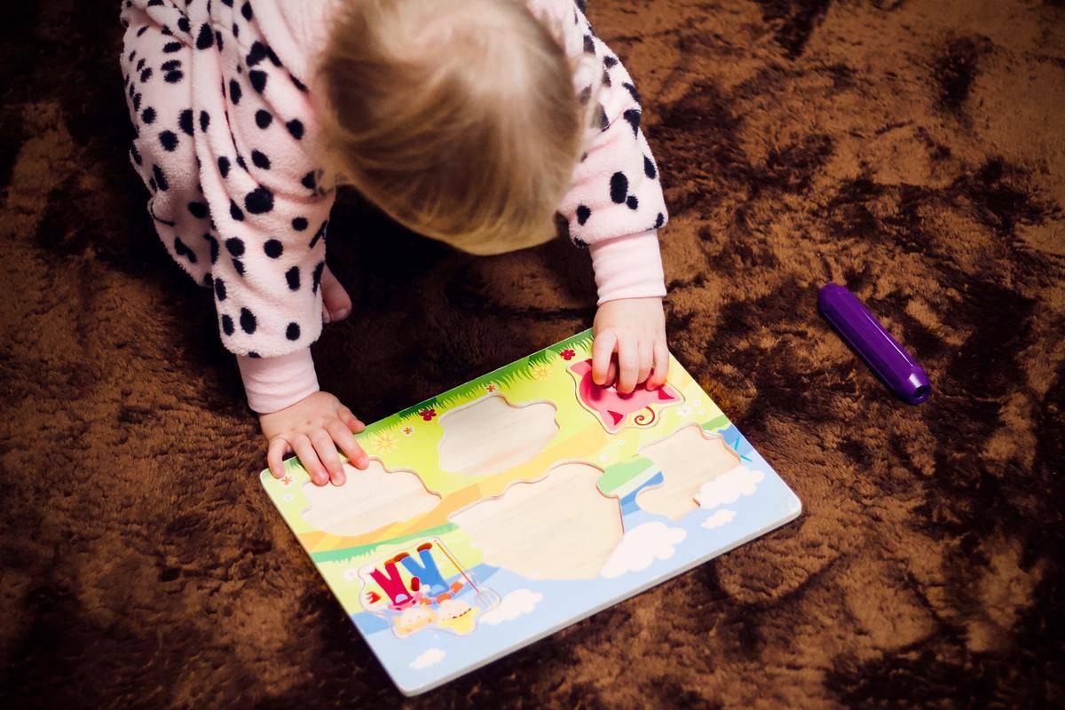 little girl attempting puzzle mat