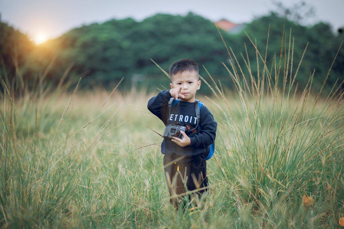 small boy standing in tall grass pointing