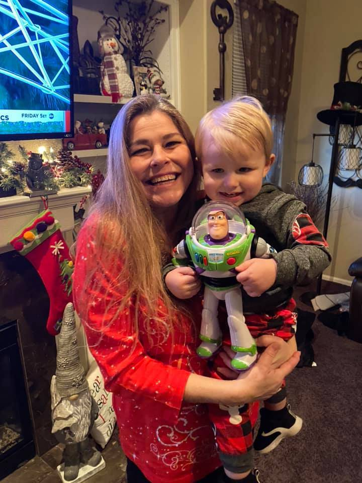 mom holding her son who is holding a Buzz Lightyear toy
