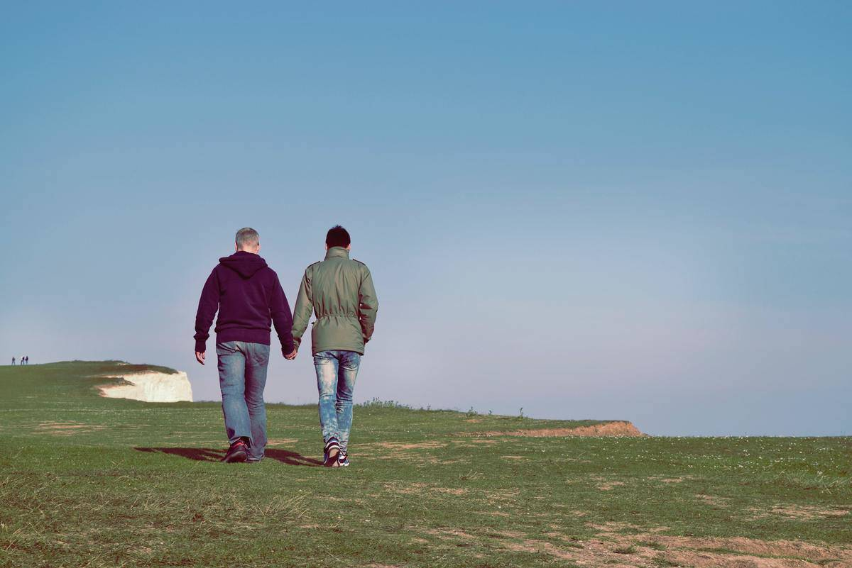 two men holding hands walking over greenspace