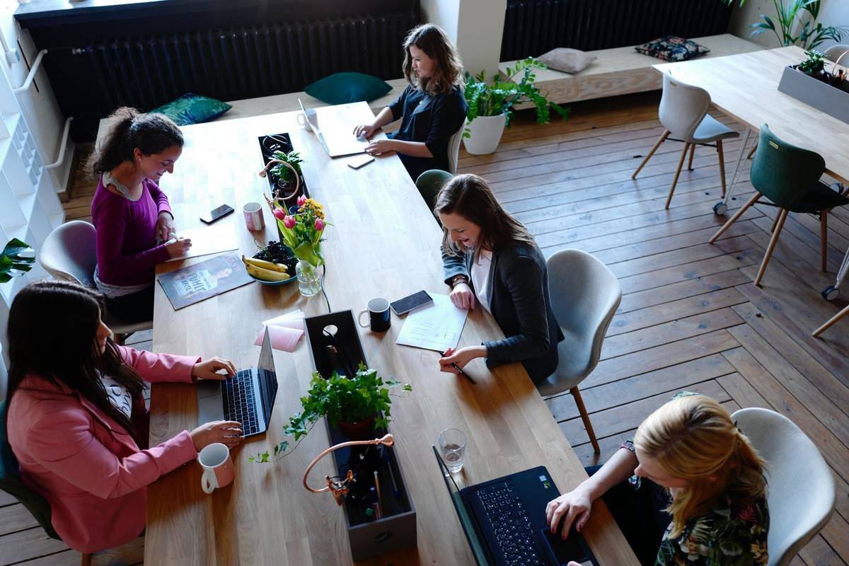 five women sitting at long wooden table working in office