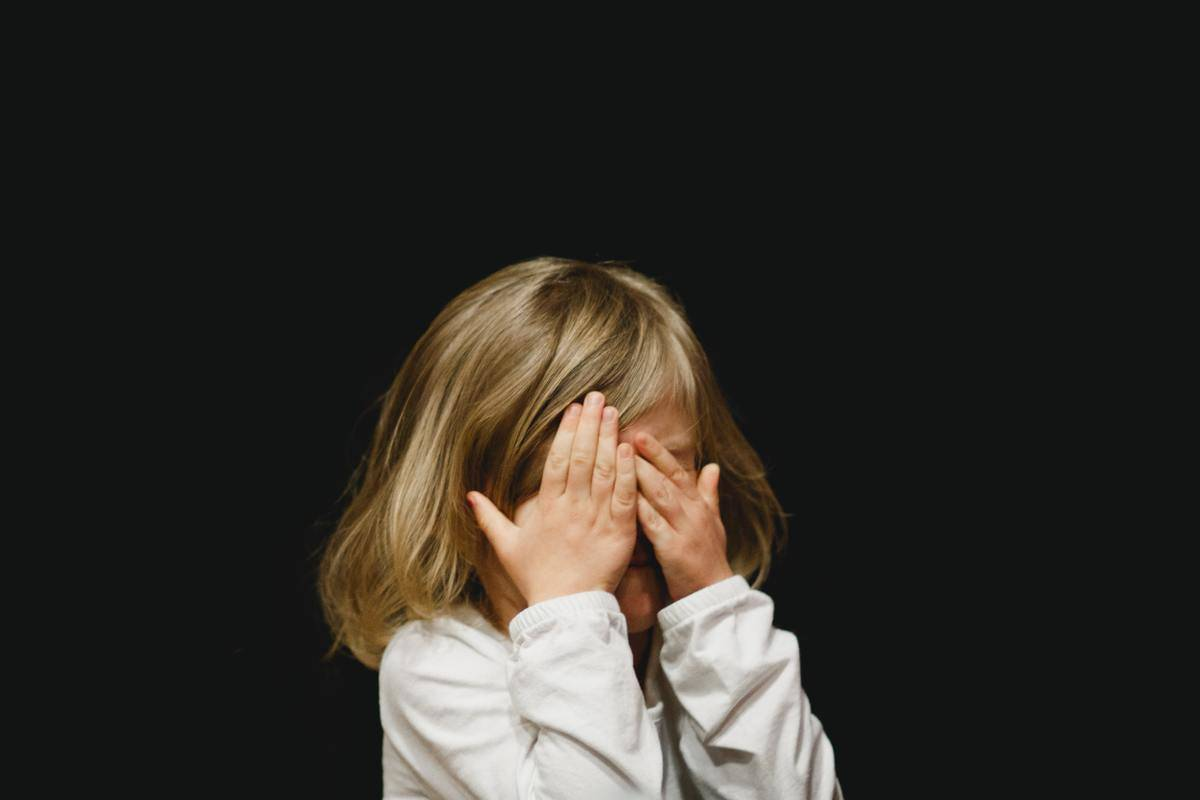 child with hands up hiding their face