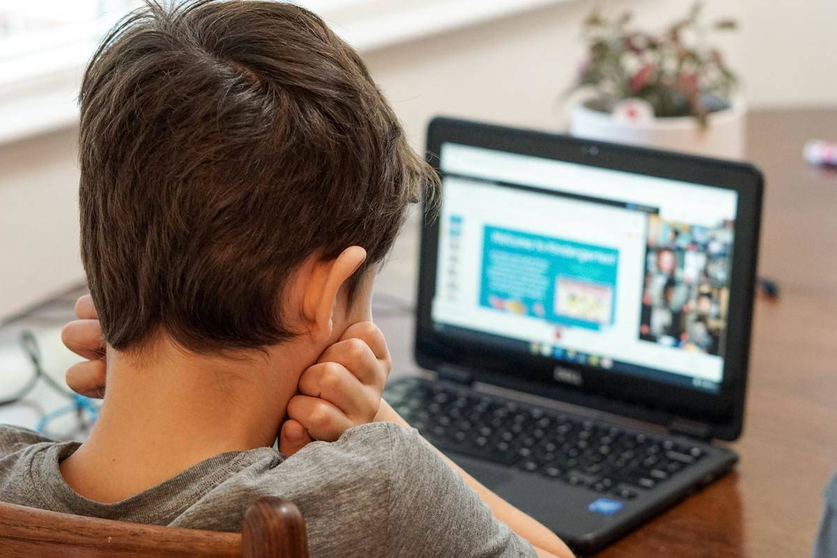 young boy sitting in front of laptop