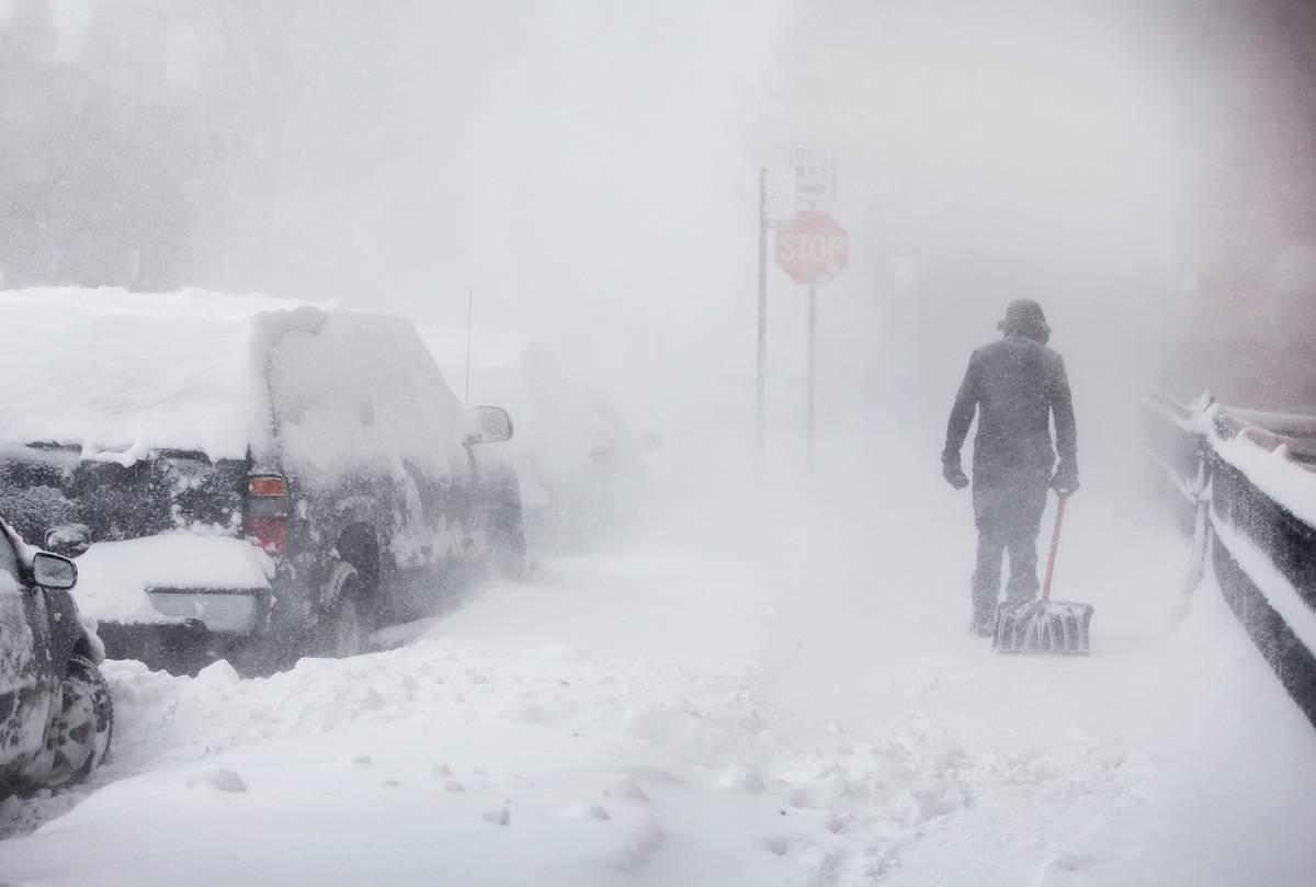 man walking in blizzard pulling shovel