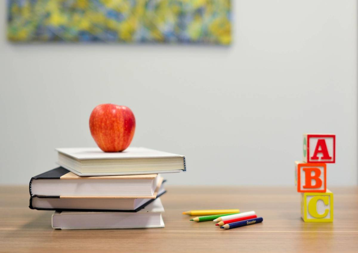 desk with books, letter blocks, and an apple