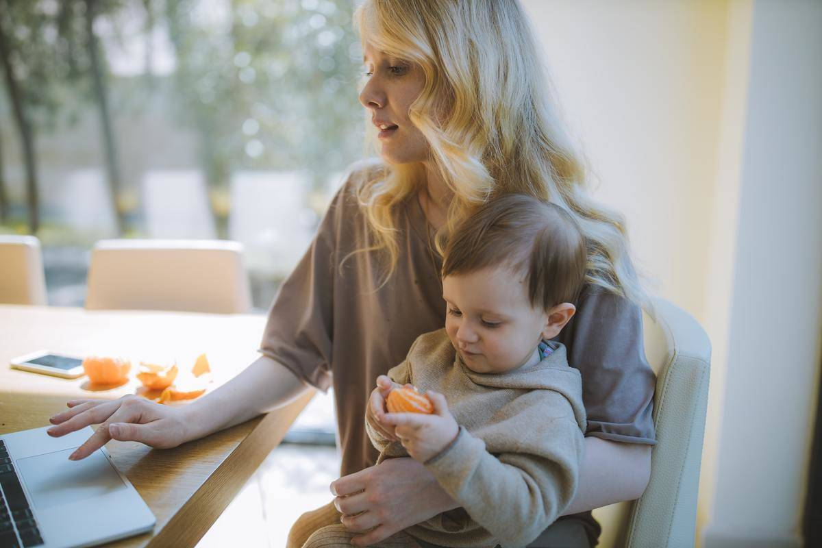 toddler sitting on mom's lap, holding a clementine, while she works