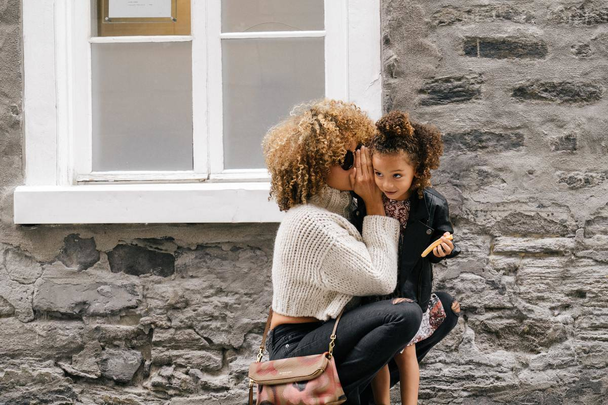 mom whispering into daughter's ear