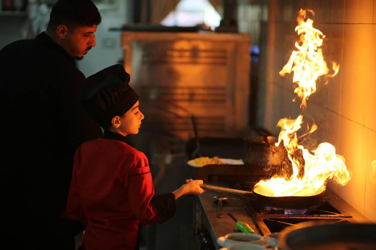Small boy in red chefs coat and black hat holding flaming sauté pan over stove.