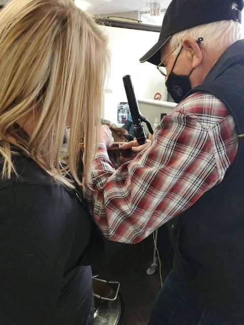 Elderly man in red flannel shirt and vest is taught by blonde woman to curl hair on mannequin