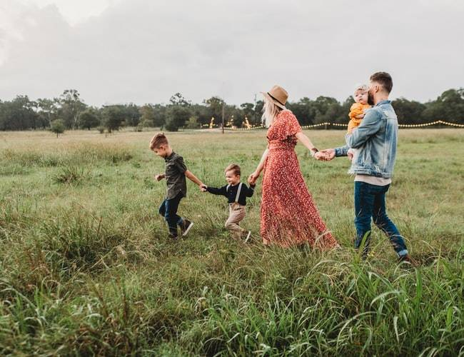family of five walking in a field as the parents hold hands