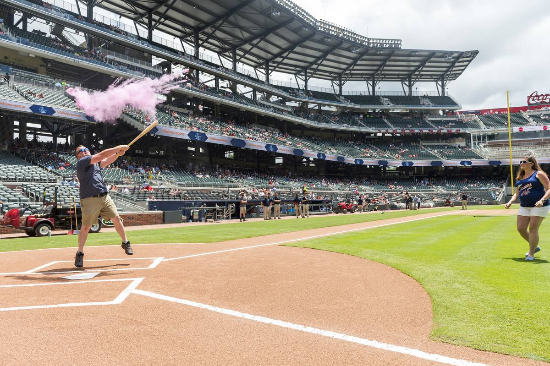 man swings bat for paternity reveal at ballpark