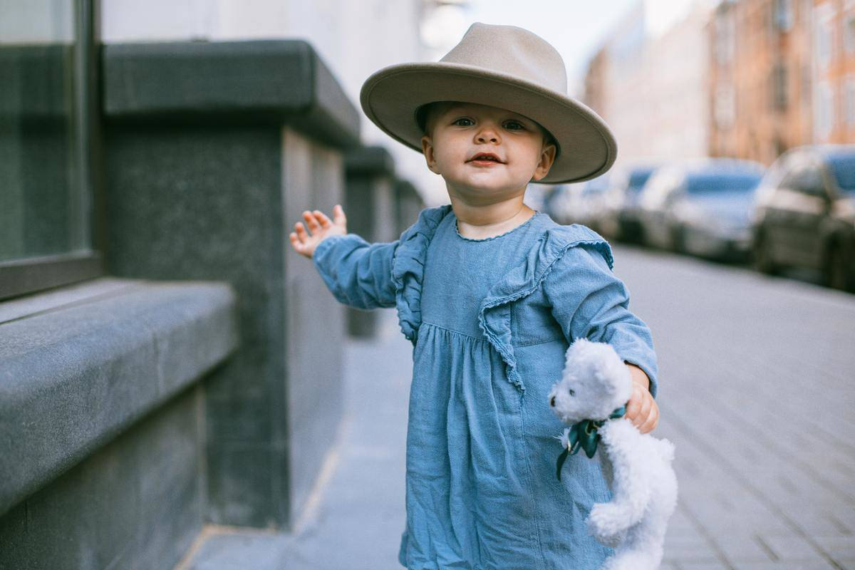 baby girl in dress and fashionable hat