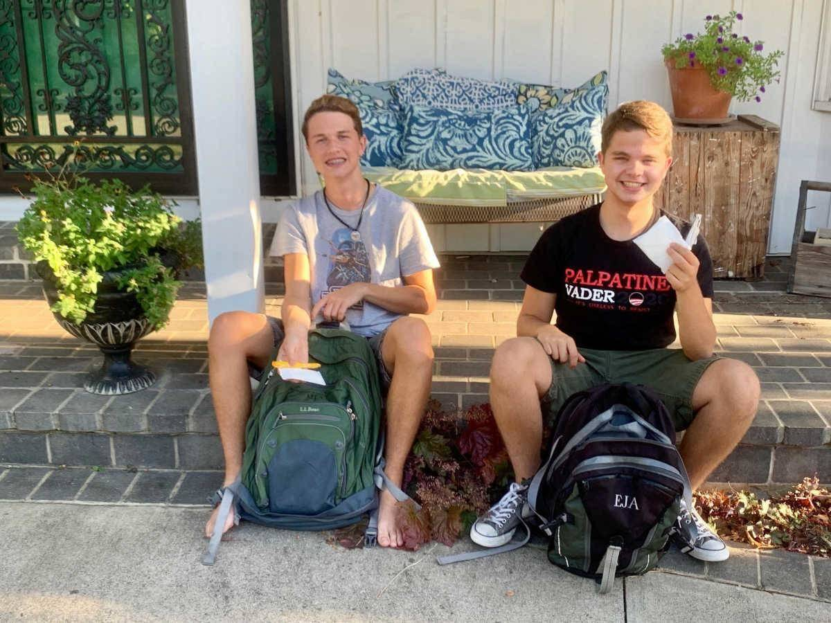 boys sitting in front of their backpacks holding up period products