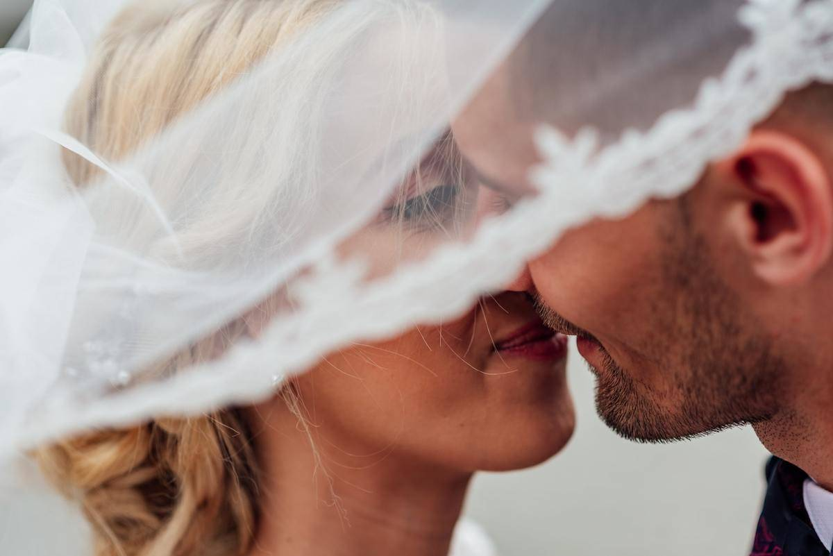 bride and groom under veil kiss