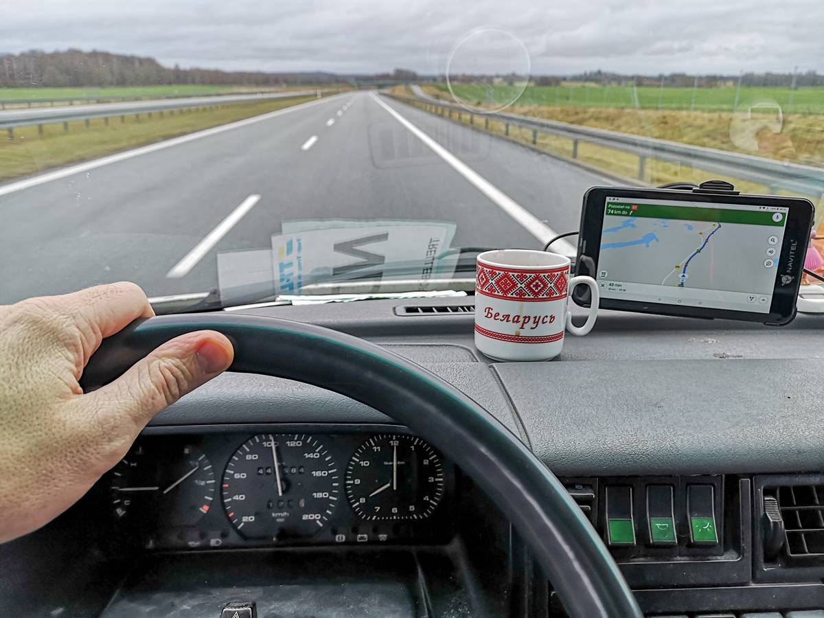 View from the inside of the van with shaking head doll , car sat navigation and cup of coffee with a Belarus inscription and historical Belarussian fancywork is seen in Gdansk
