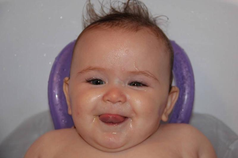 baby lying in bath with their tongue poking out of their mouth and hair sticking up