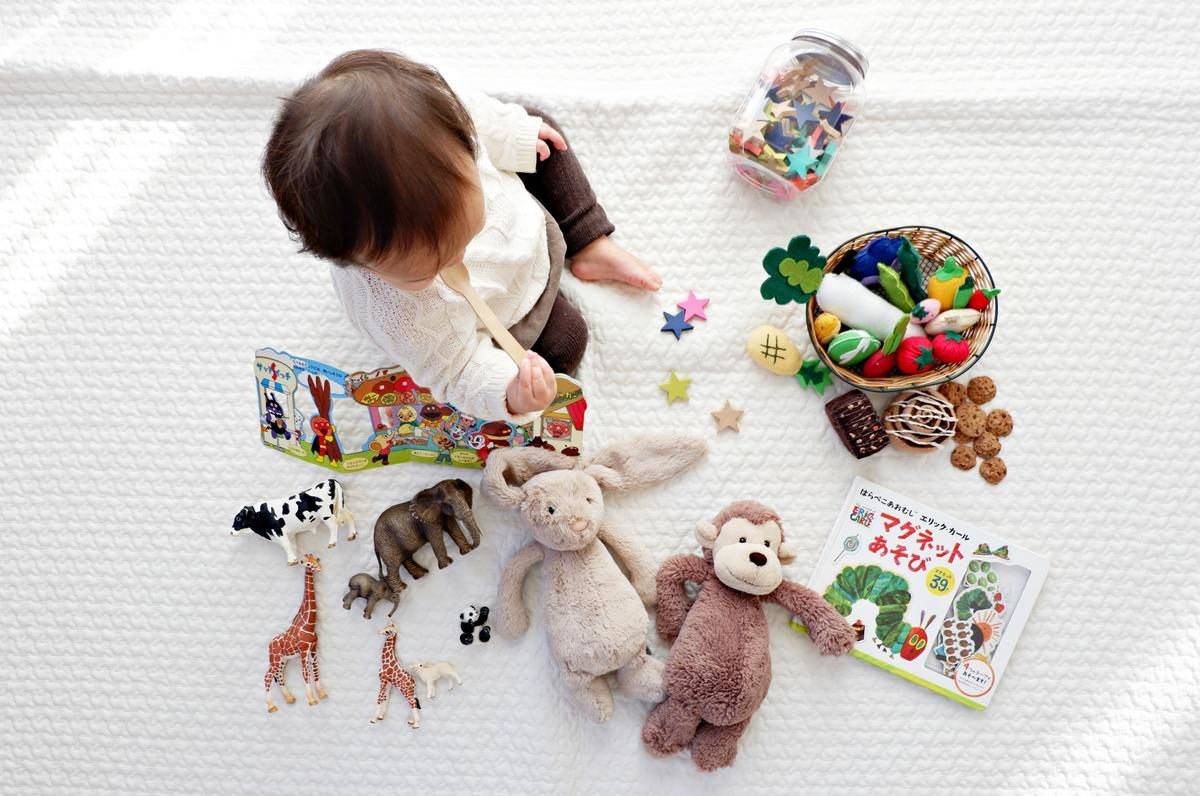 kid playing with toys on a white blanket