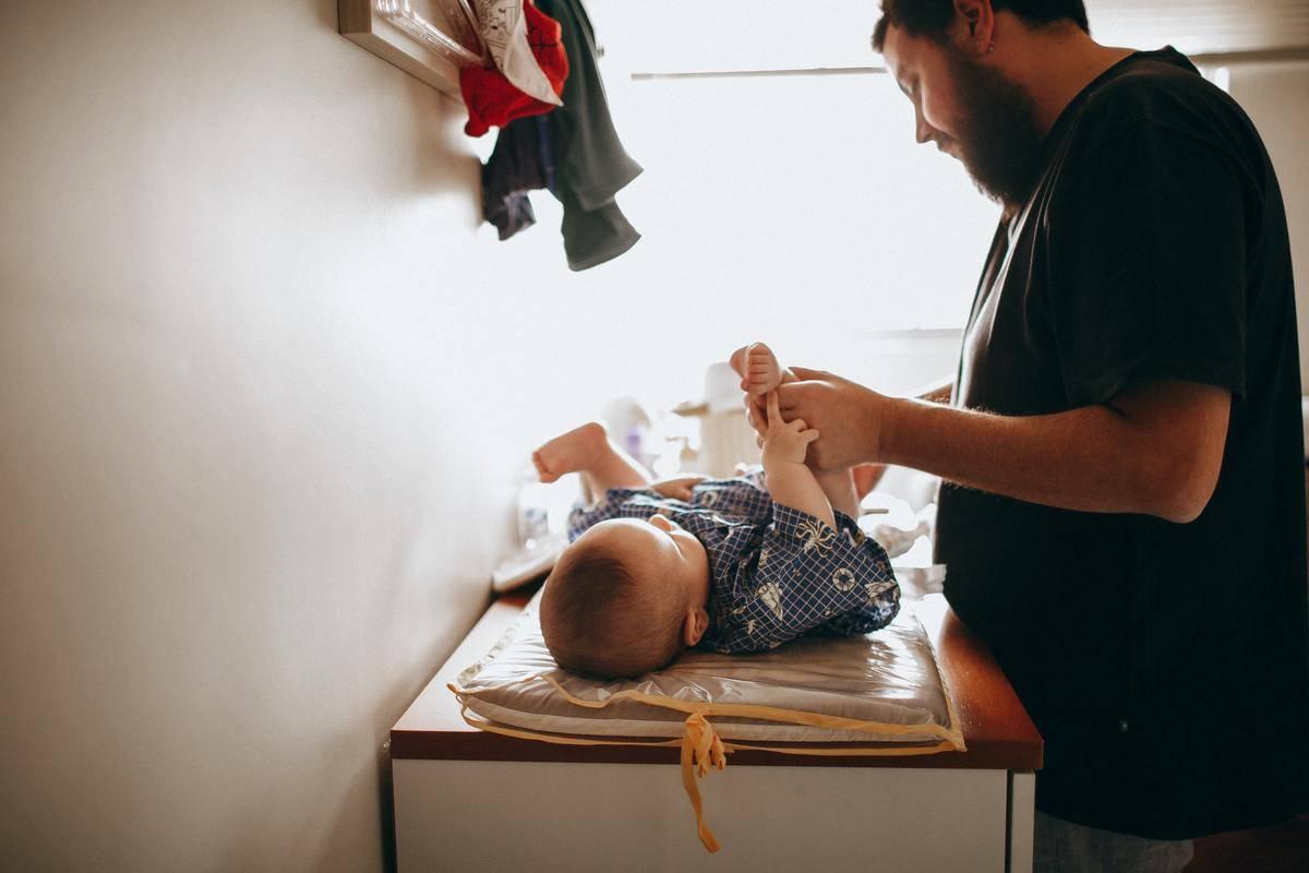 man changing baby's diaper