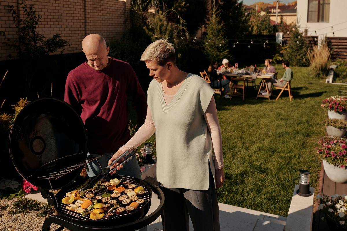 man and woman standing at grill