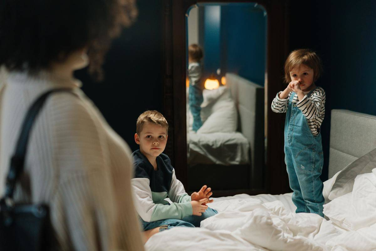 two kids on bed with mom