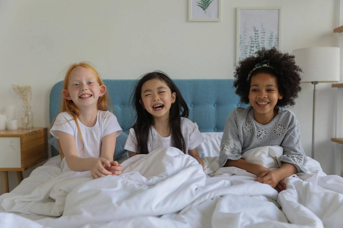 three girls laughing seated in bed