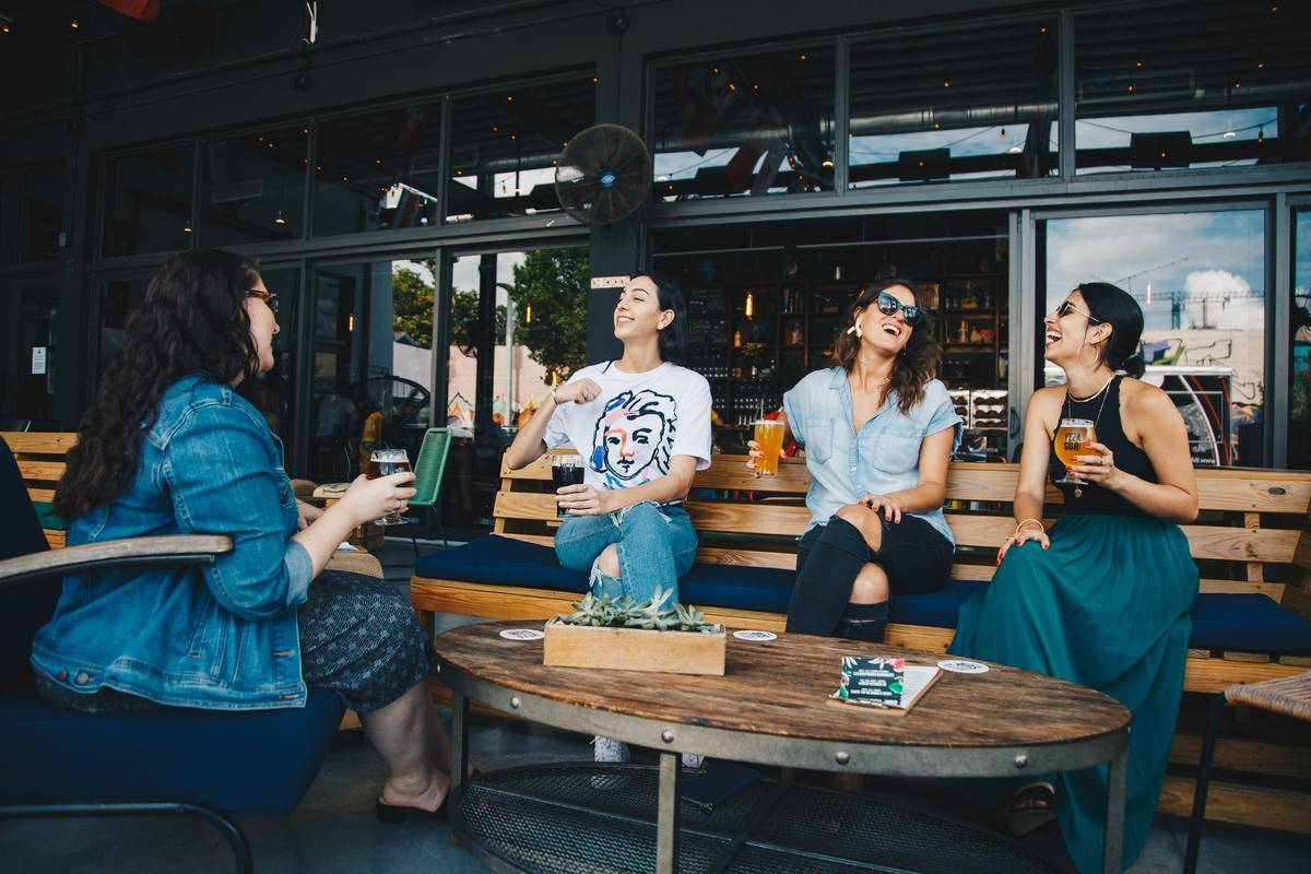 group of women laughing outdoors with coffee