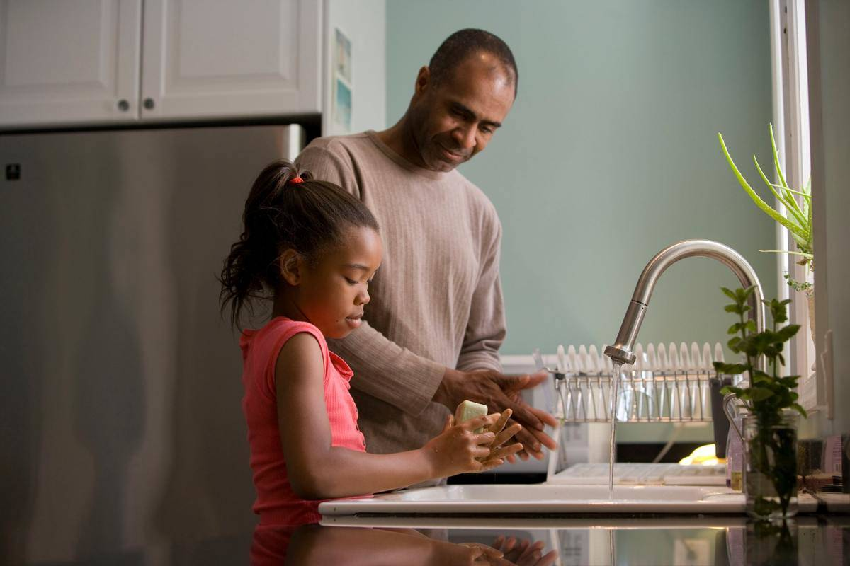 Dad and daughter washing hands at kitchen sink, silver stainless steel tap.