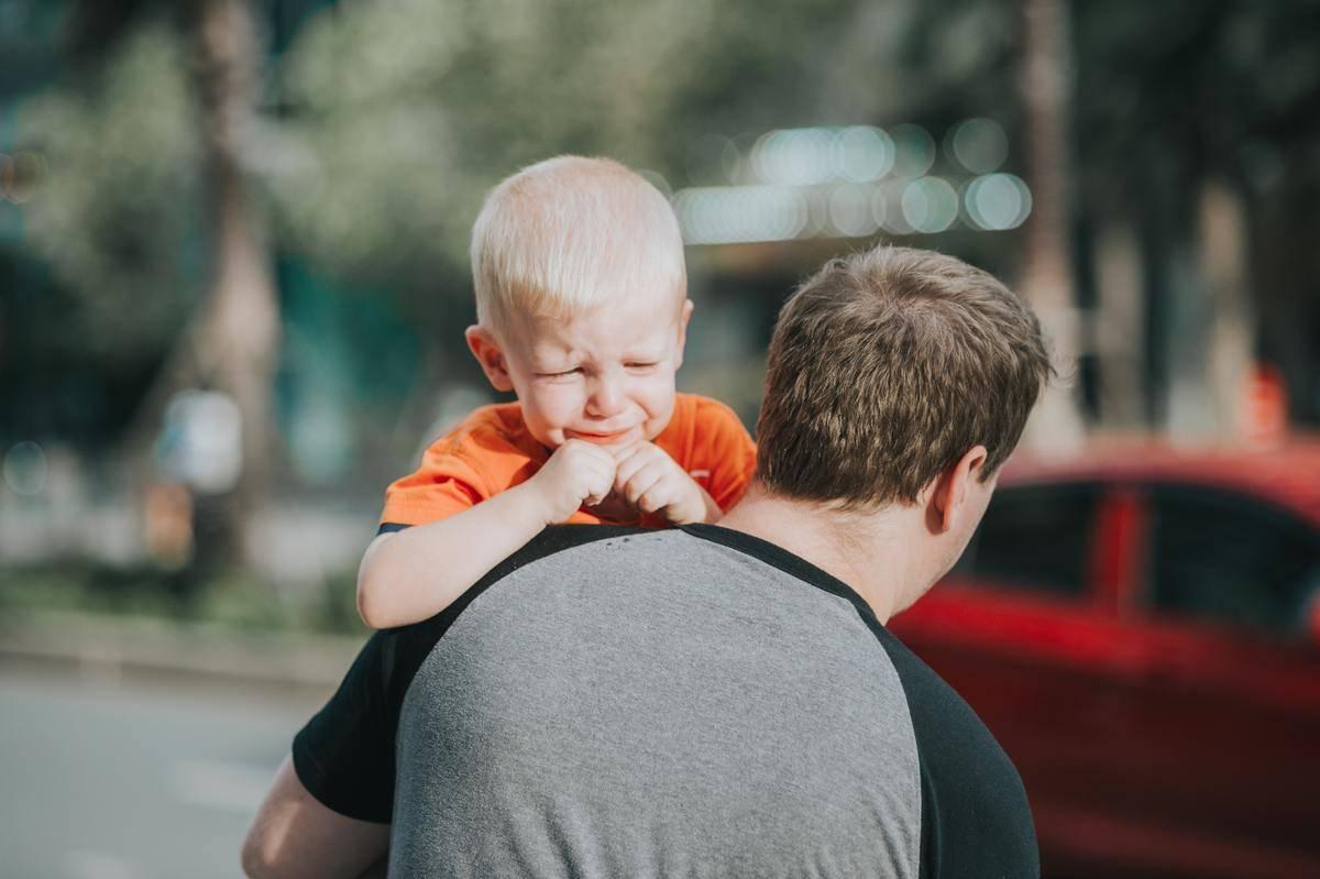 Dad in grey shirt carrying small child wearing orange shirt.