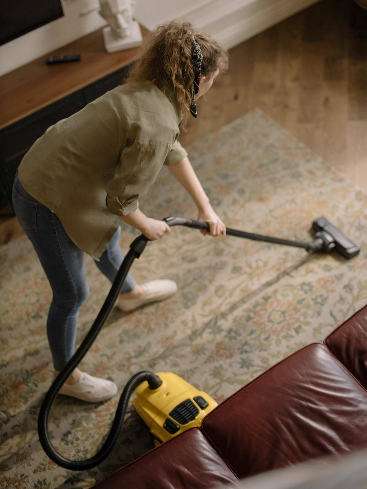 Woman vacuums area rug with yellow vacuum