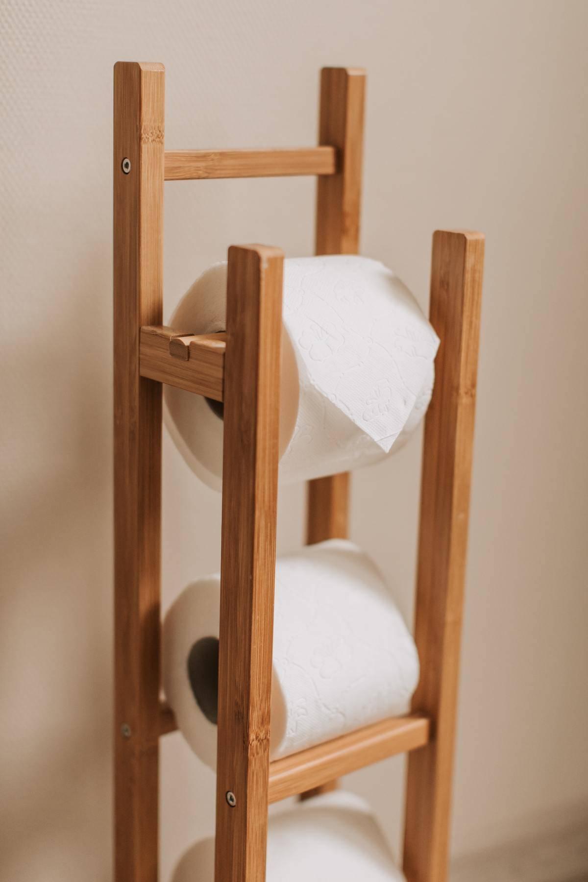 Three toilet Paper Rolls On Wooden Holder Rack